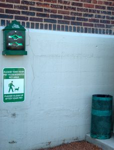 A condo association that provides a waste deposit area along an outside wall, for the convenience of its residents' dog walkers.